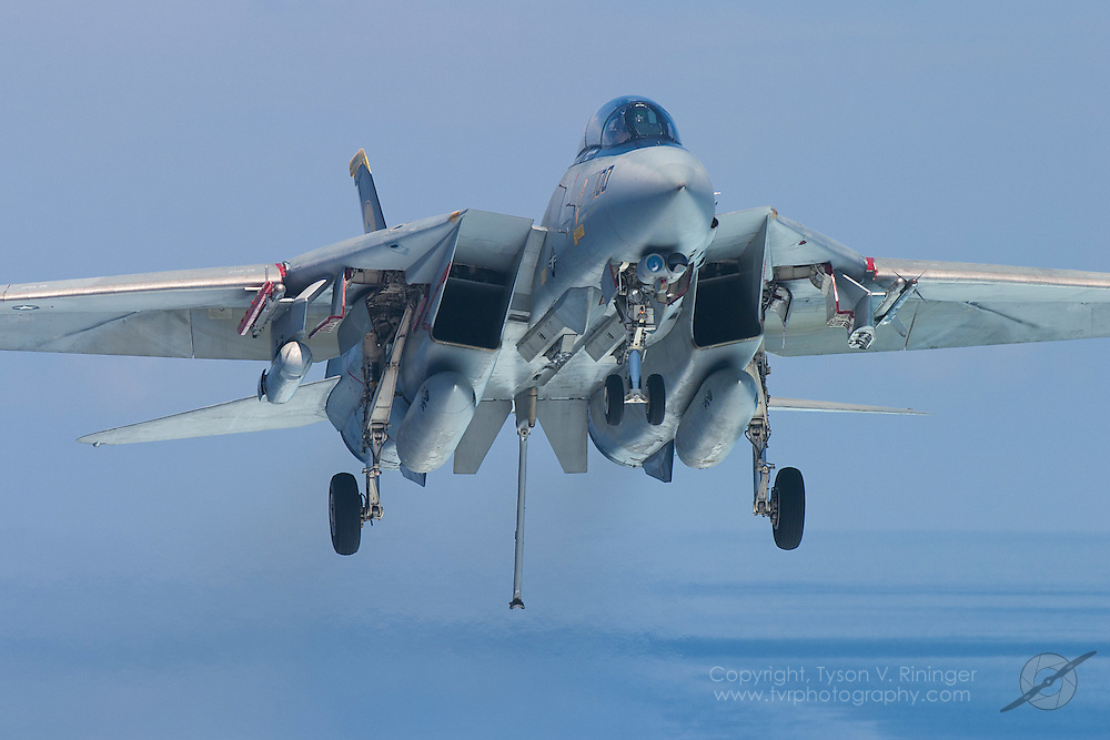 AJ100, an F-14 Tomcat from VF-31 'Tomcatters', is on approach for a trap aboard the deck of the USS Theodore Roosevelt CVN-71 during sea trials prior to their 2005 Mediterranean deployment. This would be the final cruise for the F-14 Tomcat and the last time it would ever see combat.