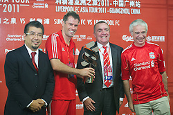 GUANGZHOU, CHINA - Wednesday, July 13, 2011: Liverpool's Jamie Carragher is presented with a trophy by Standard Chartered Chief-Executive Peter Sands (R) and Commercial Director Ian Ayre after the 4-3 win over Guangdong Sunray Cave during the first pre-season friendly on day three of the club's Asia Tour at the Tianhe Stadium. (Photo by David Rawcliffe/Propaganda)