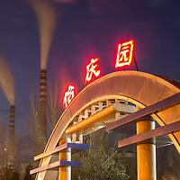China, Shanxi Province, Datong, Steam and smoke rises from smokestacks at Datong No. 2 Power Station near neon-lit city park