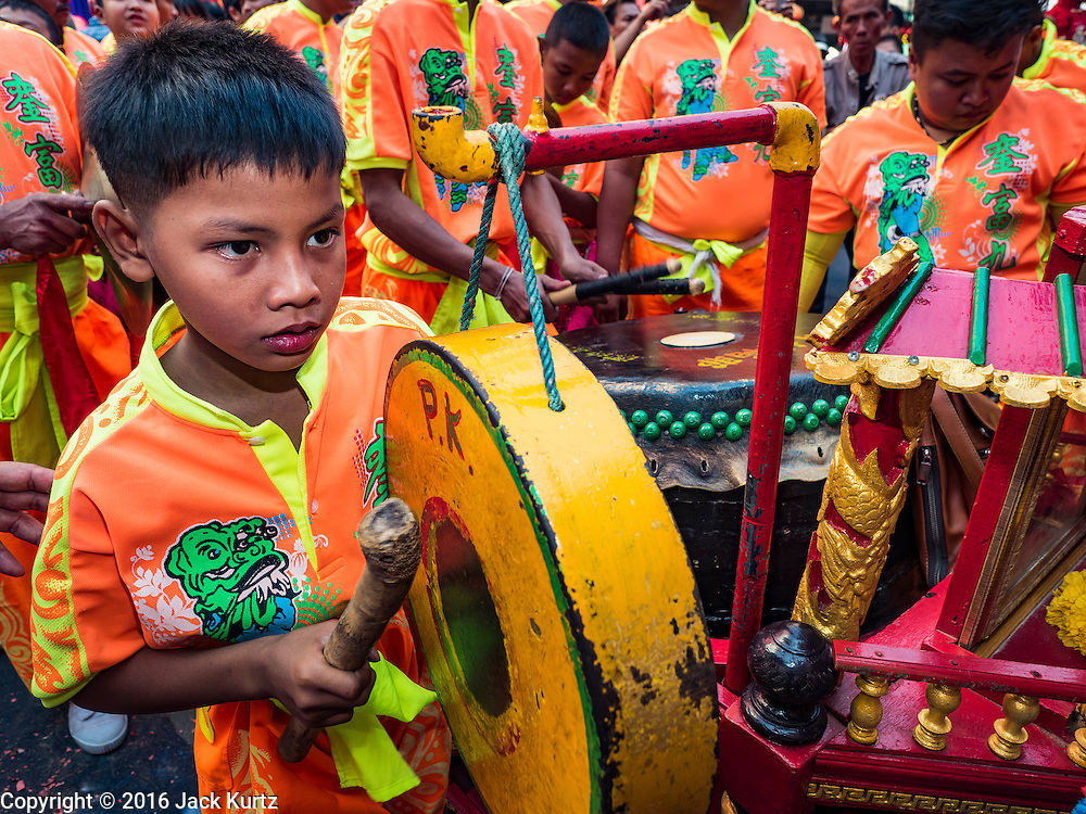 "08 FEBRUARY 2016 - BANGKOK, THAILAND:  A child plays a gong during a New Year's parade in Bangkok's Chinatown district during the celebration of the Lunar New Year. Chinese New Year is also called Lunar New Year or Tet (in Vietnamese communities). This year is the ""Year of the Monkey."" Thailand has the largest overseas Chinese population in the world; about 14 percent of Thais are of Chinese ancestry and some Chinese holidays, especially Chinese New Year, are widely celebrated in Thailand.      PHOTO BY JACK KURTZ"