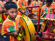 """08 FEBRUARY 2016 - BANGKOK, THAILAND:  A child plays a gong during a New Year's parade in Bangkok's Chinatown district during the celebration of the Lunar New Year. Chinese New Year is also called Lunar New Year or Tet (in Vietnamese communities). This year is the """"Year of the Monkey."""" Thailand has the largest overseas Chinese population in the world; about 14 percent of Thais are of Chinese ancestry and some Chinese holidays, especially Chinese New Year, are widely celebrated in Thailand.      PHOTO BY JACK KURTZ"""