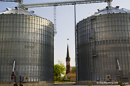 Historic St Marys Catholic Church is framed by grain bins and small plane flying overhead in Utica Illinois