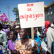 "Women from the International Lawyer's Office (BAI) Women's Network carry a sign that reads, ""No to Occupation"" as they call for the withdrawal of UN military troops from Haiti. (Photo by Ben Depp)"