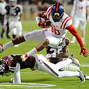 Texas A&M defensive back De'Vante Harris (1) and defensive back Devonta Burns (26) tackle Mississippi wide receiver Cody Core (88) during the first half of an NCAA college football game in College Station, Texas, Saturday, Oct. 11, 2014. (Photo/Thomas Graning)
