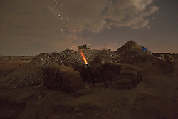 © Licensed to London News Pictures. o01/09/2015. Bashiqa, Iraq. A fighter belonging to Iranian Kurdish peshmerga from PAK fires a 60mm mortar from defensive emplacements on the summit of Bashiqa Mountain at ISIS locations within the town of the same name.<br /> <br /> Bashiqa Mountain, towering over the town of the same name, is now a heavily fortified front line. Kurdish peshmerga, having withdrawn to the mountain after the August 2014 ISIS offensive, now watch over Islamic State held territory from their sandbagged high-ground positions. Regular exchanges of fire take place between the Kurds and the Islamic militants with the occupied Iraqi city of Mosul forming the backdrop.<br /> <br /> The town of Bashiqa, a formerly mixed town that had a population of Yazidi, Kurd, Arab and Shabak, now lies empty apart from insurgents. Along with several other urban sprawls the town forms one of the gateways to Iraq's second largest city that will need to be dealt with should the Kurds be called to advance on Mosul. Photo credit: Matt Cetti-Roberts/LNP