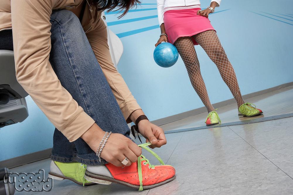 Young Woman Tying Bowling Shoes
