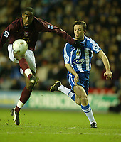Photo: Aidan Ellis.<br /> Wigan Athletic v Arsenal. Carling Cup. Semi Final, 1st Leg.<br /> 10/01/2006.<br /> Arsenal's Johan Djourou beats Wigan's David Connolly to the ball