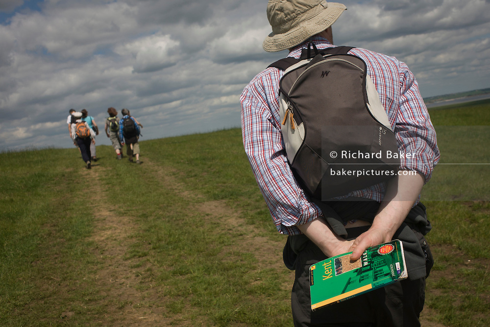 A group of country ramblers walk down a slope of grassland near Halstow on the Kent Thames estuary marshes, potentially threatened by the future London airport.