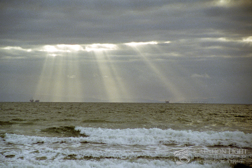 Light rays from the sun breaking through stormy clouds off the coast in Huntington Beach, California