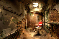 An abandoned old barber chair sits in a decaying jail cell at Eastern State Penitentiary in Philadelphia, PA.