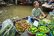 "17 NOVEMBER 2012 - BANGKOK, THAILAND:  A woman sells produce in a floating market in the Thonburi section of Bangkok. Floating markets are common in parts of Thailand with lots of canals. Bangkok used to be known as the ""Venice of the East"" because of the number of waterways the criss crossed the city. Now most of the waterways have been filled in but boats and ships still play an important role in daily life in Bangkok. Thousands of people commute to work daily on the Chao Phraya Express Boats and fast boats that ply Khlong Saen Saeb or use boats to get around on the canals on the Thonburi side of the river. Boats are used to haul commodities through the city to deep water ports for export.    PHOTO BY JACK KURTZ"