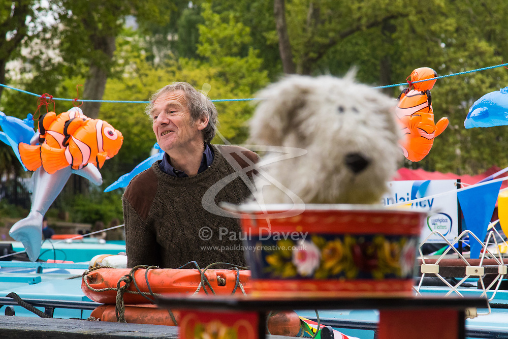 Little Venice, London, April 30th 2017. Narrowboaters from all over the UK gather for the annual Canalway Cavalcade, held on the May Day Bank holiday weekend, organised by the Inland Waterways Association, where boaters get the chance to display their immaculately prepared and brightly painted craft as well as compete in various manoeuvring tests. PICTURED: A stuffed toy dog stares out across the moored boats as a narrow boater behind calls to a friend.