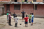 A Nepalese instructor gets the young boys to stand in a circle holding hands in during a football session in the back yard of the Voice of Children rehabilitation center in Kathmandu, Nepal. The not-for-profit organisation supports street children and those who are at risk of sexual abuse through educational and vocational training opportunities, health services and psychosocial counseling.