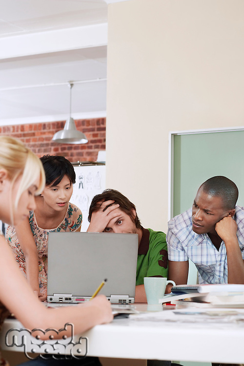 Group of tensed multiethnic business people using laptop in office