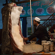 Uyghur man selling ice cream in night market, Hotan, Xinjiang Uyghur autonomous region, China. A huge piece of ice is dubiously hidden under a blanket. Starting in the middle, the vendor scrapes off some ice and then tops it off with syrup.
