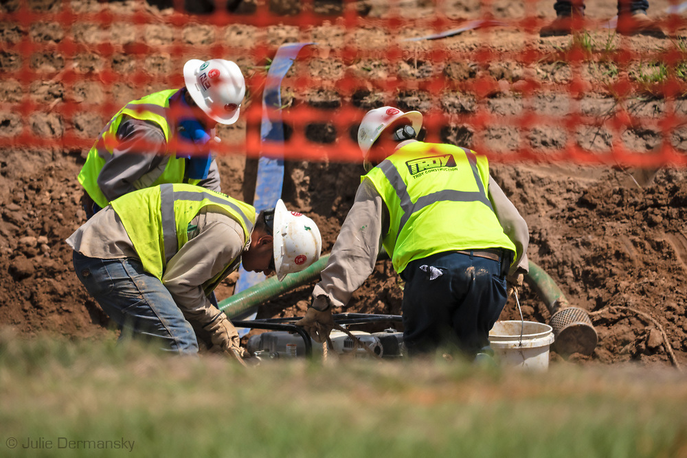 Construction crew sucing water out of the trench that the  Bayou Bridge Pipeline is in before covering the pipeline with dirt, next to Melinda Tillies house in Youngsville, Louisiana from her kitchen. <br /> The pipeline was installed about 25 feet from her home on her neighbors land.  There are no federal rules about how close a pipeline can be built next to a home.