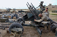 Sgt. Salvatore Broes III, left, from Dawsonville GA, and Spec. Json Verespej, right, both with U.S. Army Engineers from the 173rd Brigade Combat Support Company, from Vicenza, Italy look over recovered anti aircraft gun that was sitting among some of the weapons and ammo they returned to munitions bunkers at air base in Kirkuk after they went out into the northern Iraqi city of Kirkuk to recover caches of Iraqi military weapons and munitions to keep them from falling into the hands of Saddam loyalist and to make the town safer for its residents. Tons of explosive shells were stored at a school and were left strewn around a neighborhood soccer field.(Alan Lessig/Army Times)