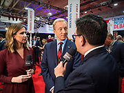 """14 JANUARY 2020 - DES MOINES, IOWA: California businessman TOM STEYER talks to reporters from CBS Television in the """"spin room"""" after the CNN Democratic Presidential Debate on the campus of Drake University in Des Moines. This is the last debate before the Iowa Caucuses on Feb. 3.    PHOTO BY JACK KURTZ"""