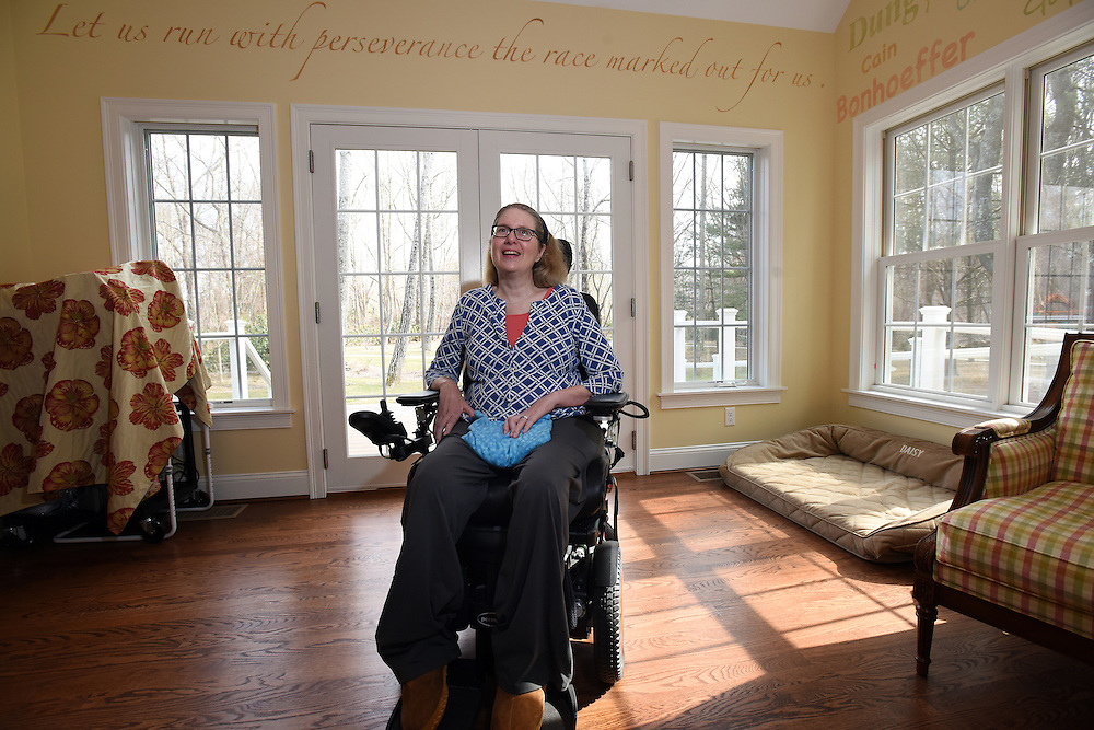 Mara Lavitt -- Special to the Hartford Courant<br /> March 7, 2016, Marlborough<br /> Pastor Nancy Butler at home in her Marlborough bedroom March 7. Above her is a passage from the bible. &ldquo;It&rsquo;s from the book of Hebrews,&quot; she said. &quot;And the early Christians were being persecuted, and they were quitting the church because it was so difficult.&quot; The whole book of Hebrews was written to bolster suffering people, she explained. &quot;That verse from Hebrews, that kind of gives me a kick in the pants when I need it.&rdquo; On the wall, right, are the names of those who inspire her.