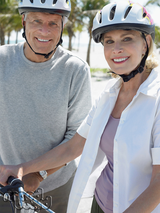 Senior couple on bicycles on tropical beach close up