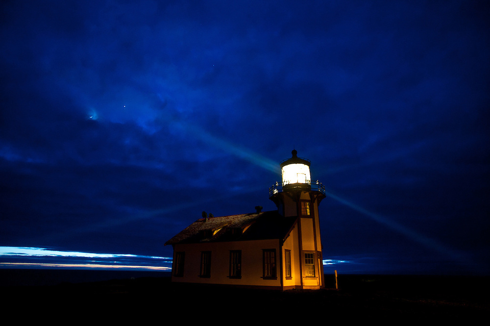 The Point Cabrillo Lighthouse shown here at dusk with a crescent moon and Jupiter in the sky. The complex is located about 1.5 miles (2.4 km) from Fort Bragg, California, and includes the lighthouse itself together with several outbuildings. Atop the lighthouse spins a third order Fresnel lens with four panels containing 90 lead glass prisms and weighing 6800 pounds, constructed by Chance Brothers, an English company, and shipped to Point Cabrillo around Cape Horn. The light is only 32 feet (9.8 m) above the ground, but because of the height of the headlands it stands 81 feet (25 m) above sea level.