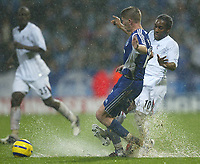 Photo: Aidan Ellis.<br /> Bolton Wanderers v Zenit St Petersburg. UEFA Cup. <br /> 03/11/2005.<br /> Bolton's Jay-Jay Okocha and Zenit's Velice Sumulikoski battle for the ball in the rain