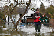Milk man delivers milk to flooded homes on Friary Island, Wraysbury near Staines. Flood waters remain high after last weeks flooding across the Thames valley. UK<br />
