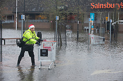 ©Licensed to London News Pictures 22/12/2019. <br /> Tonbridge ,UK. Sainburys worker collecting trolleys from flood water. Heavy rain over night has caused more Christmas flooding in Kent.  Christmas shoppers in Tonbridge, Kent are facing severe disruption in the town centre with two car parks, roads and pathways all flooded and out of action as the River Medway bursts its banks. Photo credit: Grant Falvey/LNP