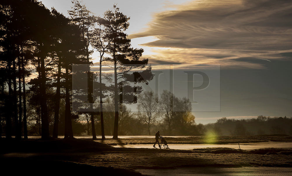 © Licensed to London News Pictures. 18/01/2017. Walton on the Hill, UK. A golfer walks on the fairway a the sun rises on a frosty Walton Heath south of London. Britain is continuing to experience a cold spell. Photo credit: Peter Macdiarmid/LNP
