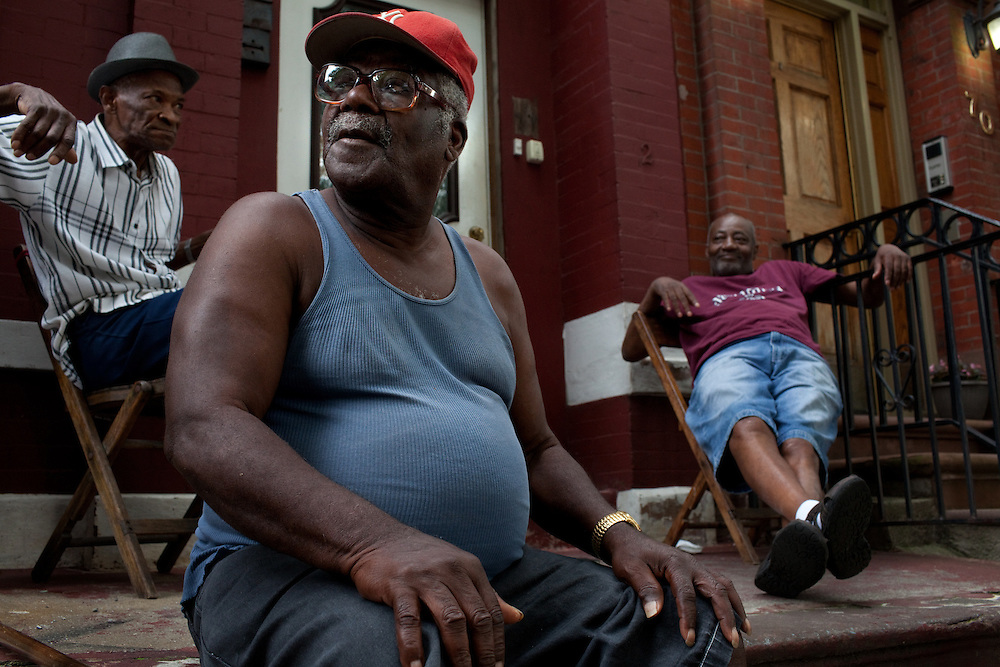 Russell Earl, left, George Marvin, center, and Edward Henderson watch passersby from their stoop in Bed-Stuy beside the Nostrandt subway stop in Brooklyn, New York on June 24, 2012.