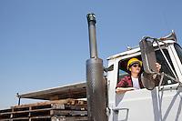 Female industrial worker adjusting mirror while sitting in logging truck