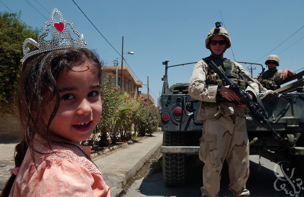 A young Iraqi girl plays near soldiers from the U.S. Army 101st Airborne 3rd Battallion 502nd Infantry as they provide security for July 28, 2003 water distribution to residents of the Northern Iraqi city of Mosul.