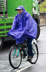 © London News Pictures. 01/05/2012. Oxford, UK. A man riding a bike while sheltering from the rain in a poncho in Oxford City centre on April 1, 2012. Photo credit : LNP