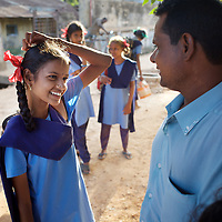 On a weekly visit, Krishnamurthy collects from school his three daughters attending Cuddalore's Government Girls High School. Smiling to him is Sivapriya (age 14)...The five Krishnamurthy sisters from Pudupettai were placed in the Government Home for Tsunami Children in Cuddalore, Tamil Nadu when they lost their mother to the 2004 tsunami. Their father, Krishnamurthy, had decided he could no longer provide day-to-day care for his daughters. Krishnamurthy later remarried. The Krishnamurthy sisters now range in age from eight to sixteen...The four younger sisters are still at the Governement home (or orphanage). In summer 2009, Sivaranjini, the eldest aged sixteen, failed her 10th Standard exams and had to drop out of school so leaving her not eligible for care at the Government home. She is now living with her father and his new wife Nagamalli's house 30km away in Pudupettai. Krishnamurthy is intending that Sivaranjini marry a second cousin in 2010. ..Krishnamurthy visits the Government orphanage once a week to see his four younger daughters. Nagamalli is popular with all five sisters. She provides them attention when they are together and is genuinely interested in their well-being. Sivapriya remains close to her paternal aunt Kamasala with whom she used to live in the fishing village of Thazanguda. Kamasala visits Sivapriya at the orphanage every fortnight. The sisters return to their father's home for festivals including Diwali and the Pudupettai village temple festival...According to Revathi, the staff member in charge at the Government home, the absence of the elder Sivaranjini has had the effect of making the remaining four sisters still at the home increasingly independent. For instance, where they used to all sleep together the girls now sleep in different dormitories. The eldest of these four, fourteen year-old Sivapriya has adopted some of the responsibilities of her elder sisters including coordinating clothes washing and helping her younger siblings with