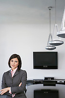 Business woman leaning against table in conference room portrait