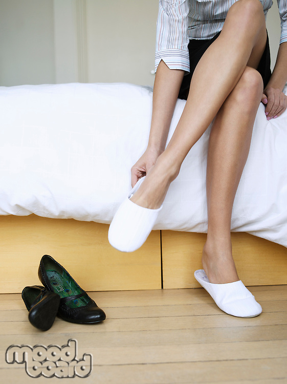 Young woman sitting on bed putting on slippers low section