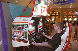 Young homeless man playing Sega Rally driving game in seaside arcade,