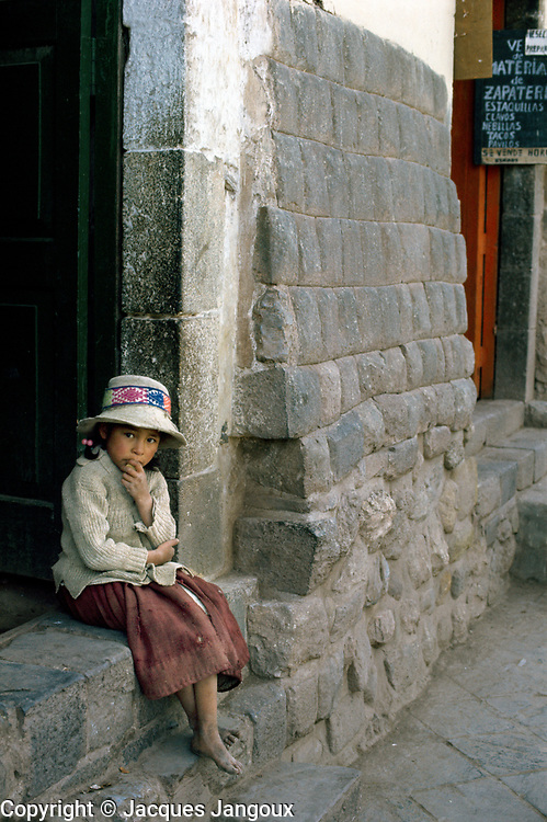 Lonely pensive Indian girl sitting in Inca wall doorway, Cuzco, Peru