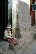 Lonely pensive Indian girl sitting in Inca wall doorway, Cuzco, Peru