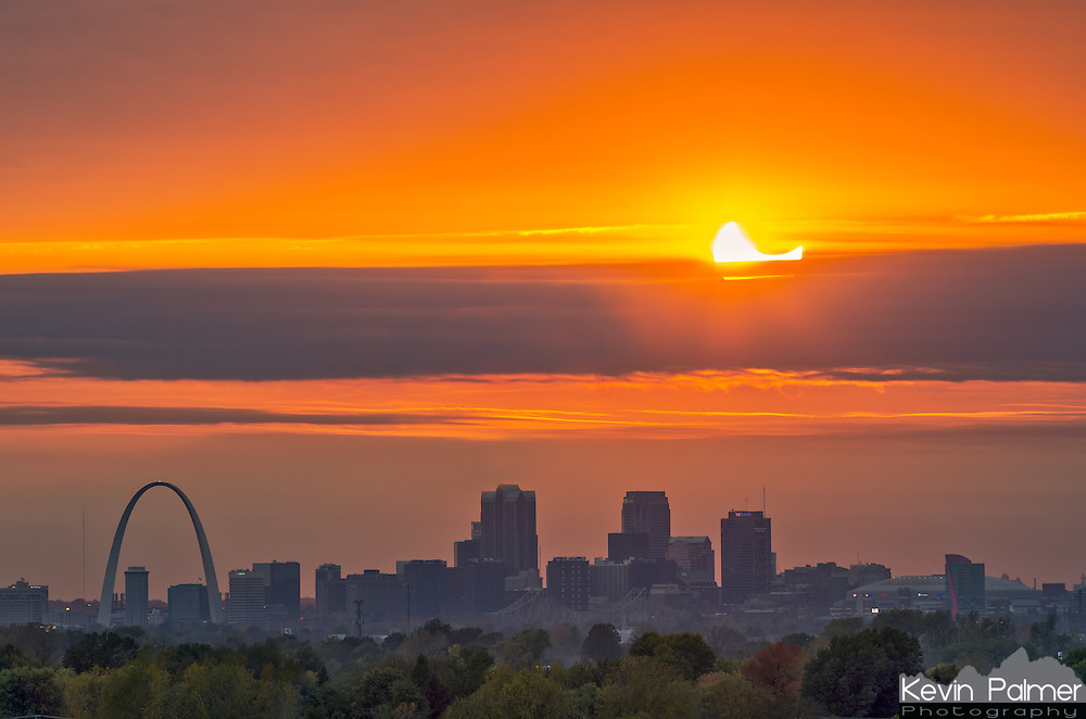 A partially eclipsed sun sets over the skyline of Saint Louis, Missouri. About 40 minutes before the sun set, it moved behind some thick clouds to the west. There was a small gap in between clouds, but it kept getting smaller. As the sun sank lower, the gap wasn't big enough to fit the entire disk of the sun. So I just shot the upper portion of the sun where the moon was. I had to time it just right, because this lasted only a few seconds. The sun looked like it would appear one more time, but it never did. <br />