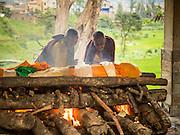 05 AUGUST 2015 - KATHMANDU, NEPAL: Buddhist monk light a funeral pyre at a cremation in Kathmandu, Nepal.    PHOTO BY JACK KURTZ