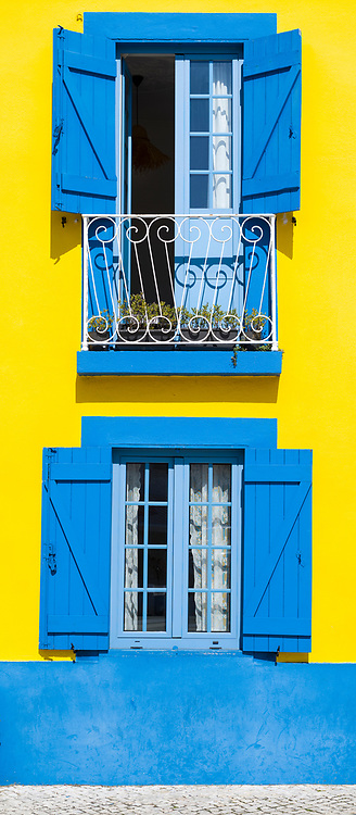 Traditional brightly coloured blue and yellow facade, balconies and shutters in Cais dos Botiroes harbour side by marina at Aveiro, Portugal