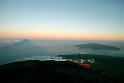 In clear sky days, sunrise is an unforgettable moment in Pico's summit. The perfect triangled shadow of the mountain is projected in the sea and in the clouds (at left) and forms with Faial island, jsut on the other side of the canal a beautiful landscape.
