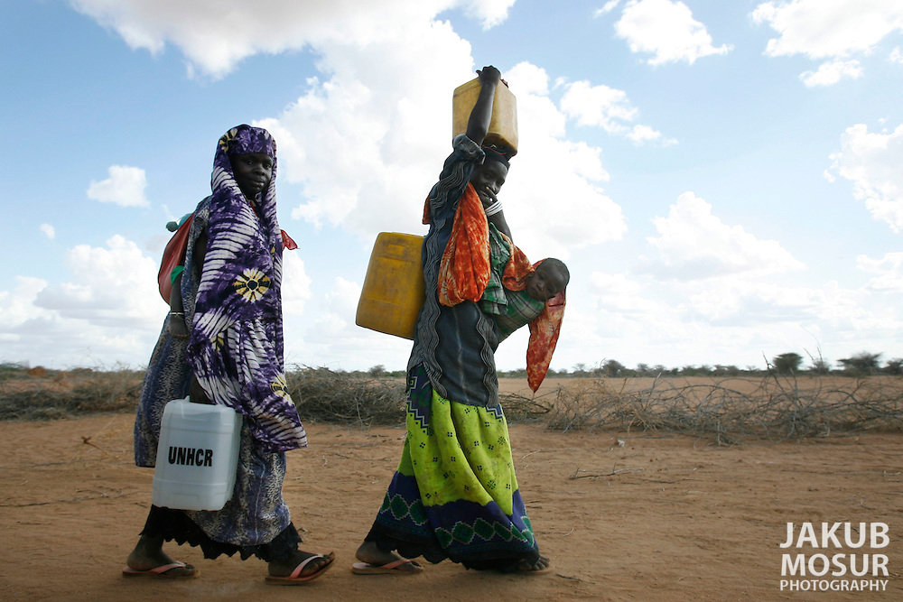 September 14, 2006 - Somali women carry water at the Dagahaley Refugee Camp in Dadaab, Kenya, 50 miles from the Somali border. Somalis are fleeing from recent clashes between Somalia Union of Islamic Courts and Somali warlords. Over 21,000 refugees since January 2006 have arrived in Dadaab which has a growing population of 140,000 refugees, in the North Eastern province of Kenya..(Photo by Jakub Mosur/Polaris)