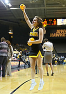 February 11 2013: An Iowa Hawkeyes cheerleader throws out mini basketballs during the first half of the NCAA women's basketball game between the Nebraska Cornhuskers and the Iowa Hawkeyes at Carver-Hawkeye Arena in Iowa City, Iowa on Monday, February 11 2013.