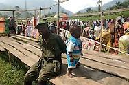 Nyabiondo. D.R.C.    A Rebel Soldier member of the FDLR plays with his baby during market day in this little village in Eastern Congo where several militias intermingle. (Photo by Miguel Juárez Lugo).