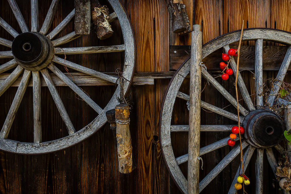 Two wooden wheels hang from the side of a traditional cottage in Ogimachi village.