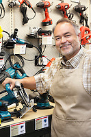 Portrait of a happy salesperson with electric saw in hardware store