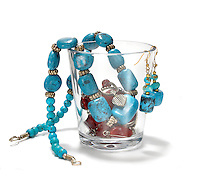 turquoise and silver necklace and earrings in a glass