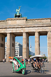 View of Brandenburg Gate in Mitte Berlin with tourists on tricycles Germany